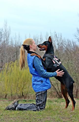 mujer y doberman abrazados